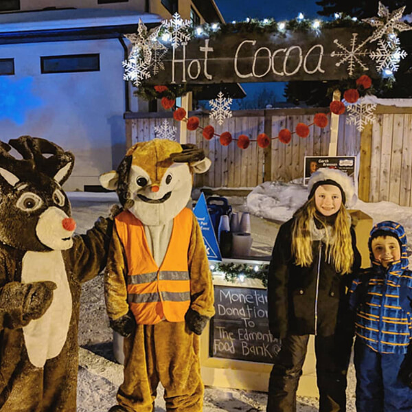 teacher's pet giving back - love heart looms - hot cocoa stand with children in costumes selling hot cocoa for donation to the edmonton food bank